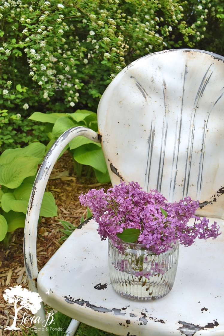 white metal lawn chair with lilacs