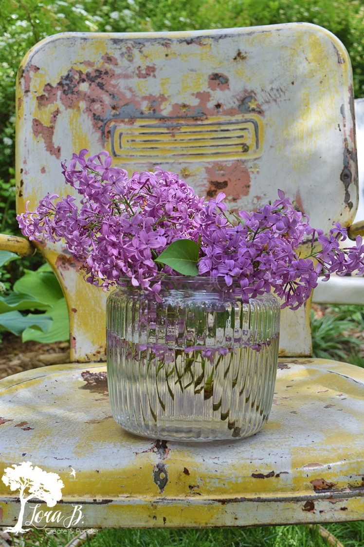 Lilacs on a vintage lawn chair.