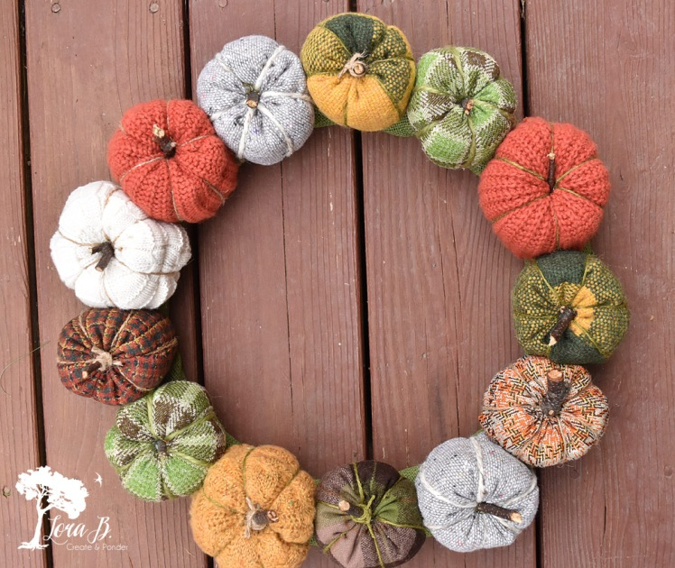 Fabric pumpkin wreath made with vintage quilt pieces and thrift store sweaters.