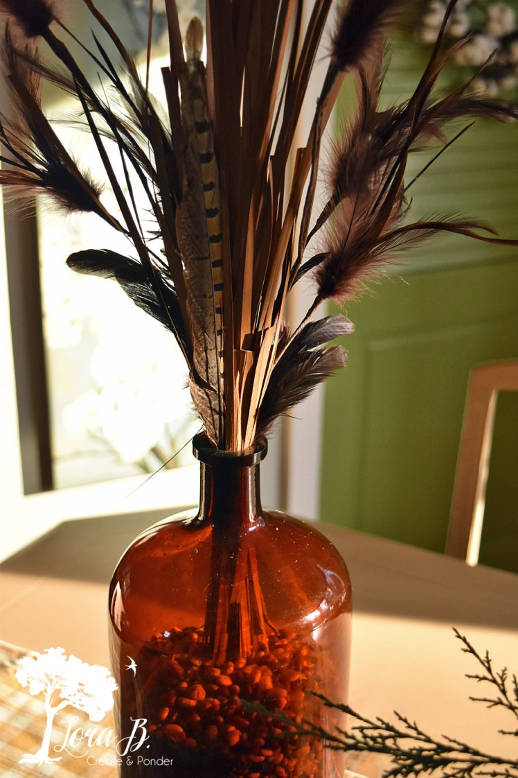 Feathers and grasses in a vintage brown bottle.